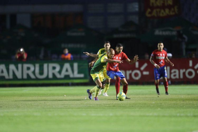 Janderson Pereira pela el balón con Sergio Trujillo.