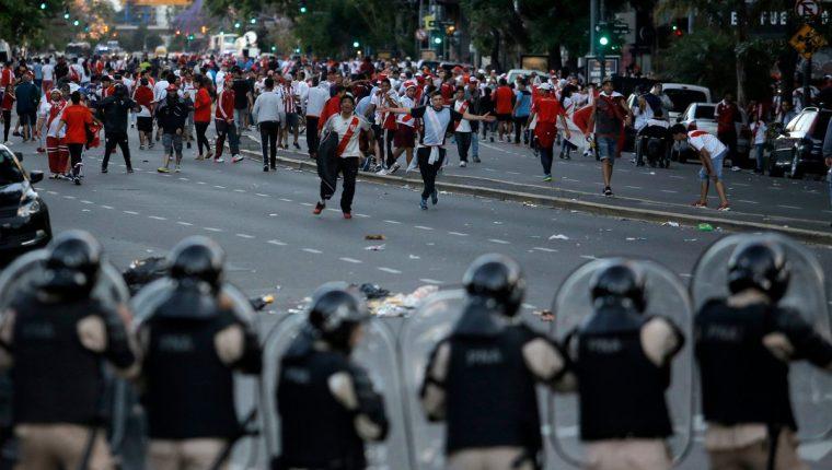 La policía antimotines trató de detener a un grupo de aficionados violentos de River Plate que causó problemas afuera del estadio Monumental. (Foto Prensa Libre: Sports Center, ESPN)