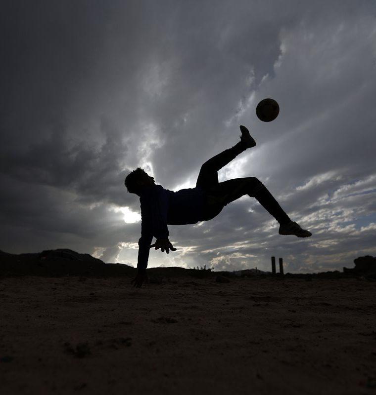 Un joven Yemeni patea el balón durante un juego de barrio con sus amigos en Sanaa. (Foto Prensa Libre: AFP)