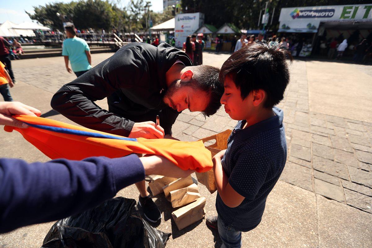 Rodrigo Saravia firma una de las camisolas que regaló. (Foto Prensa Libre: Jeniffer Gómez)