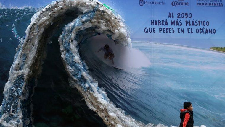 Una Manta publicitaria retrata a un hombre, surfeando una ola hecha de bolsas de plástico y botellas, para denunciar la contaminación de los océanos con motivo del Día Mundial del Medio Ambiente.(Foto prensa Libre:AFP)