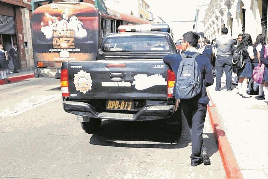 Un estudiante descansa recostado en una patrulla que resguarda un centro educativo en la zona 1. (Foto Prensa Libre: Hemeroteca PL)
