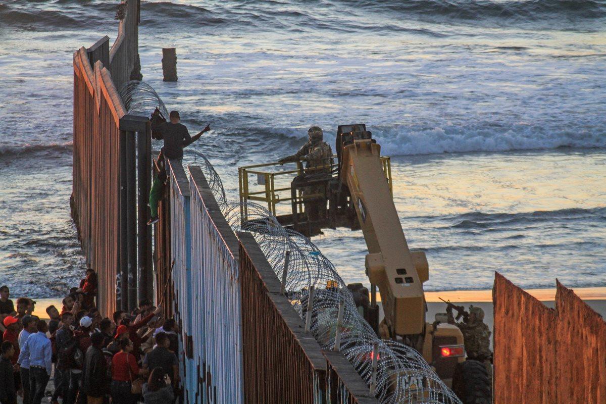 Unos migrantes trepan el muro fronterizo en Tijuana, México, mientras un soldado apunta su arma contra ellos del lado estadounidense. (Foto Prensa Libre: EFE)
