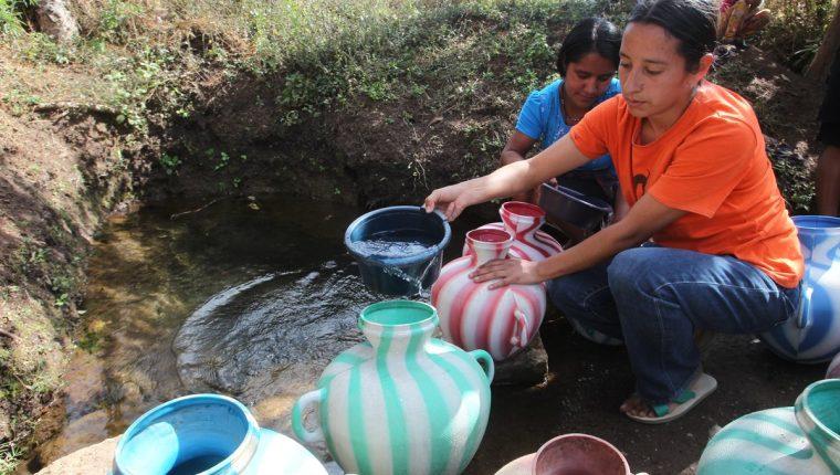 Mujeres que viven en la aldea Volcancito, Palencia, recolectan agua de un pozo natural. (Foto Prensa Libre: Hemeroteca PL)