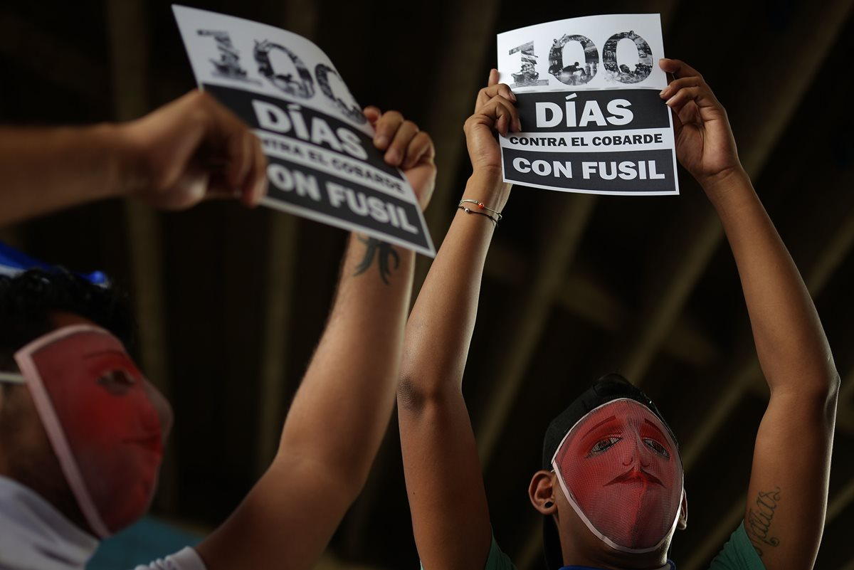 Manifestantes sostienen carteles durante una vigilia para conmemorar los 100 días de protestas contra  Ortega. (AFP)