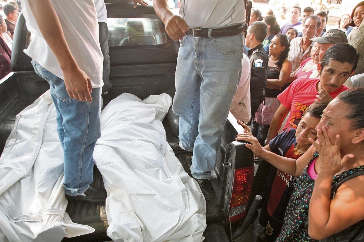 PERSONAL DEL Ministerio Público traslada los cuerpos de los periodistas Danilo López y Federico Salazar a la morgue de Mazatenango, ante escenas de llanto y dolor de familiares y amigos congregados en el lugar del ataque.