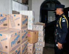 Agente de la PNC observa parte de la mercadería decomisada en Retalhuleu. (Foto Prensa Libre: Rolando Miranda)