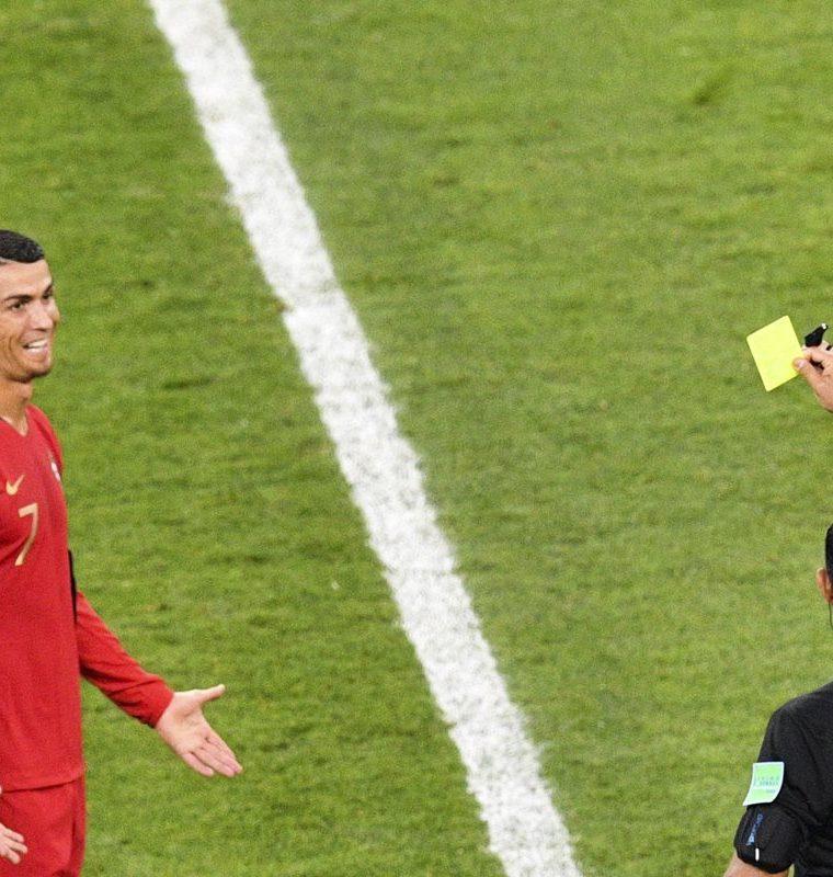 El árbitro Enrique Cáceres muestra la tarjeta amarilla a Cristiano luego de revisar el VAR. (Foto Prensa Libre: AFP)