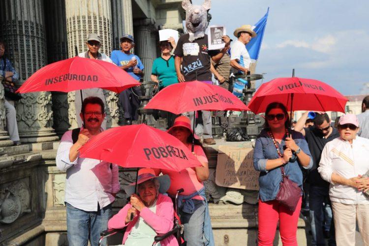Este grupo de personas escribieron en sombrillas algunos de los problemas que afectan al país
