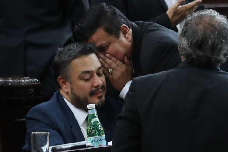 El diputado Estuardo Galdémez le habla al oído a Javier Hernández, momentos antes de iniciar la votación.