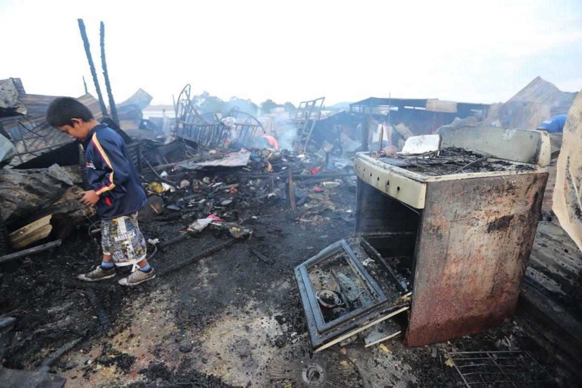 Menor camina entre los escombros que dejó el incendio. (Foto Prensa Libre: Érick Ávila).