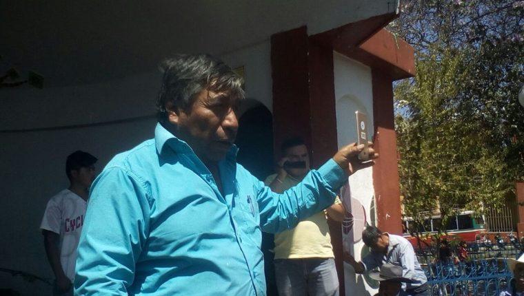 Juan Zapeta, alcalde indígena de Santa Cruz del Quiché, enseña a los vecinos el celular que fue robado. (Foto Prensa Libre: Héctor Cordero)