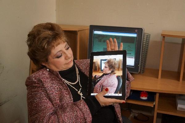 Blanca Loy, estudiante de computación, observa una fotografía tomada  con una tableta electrónica.