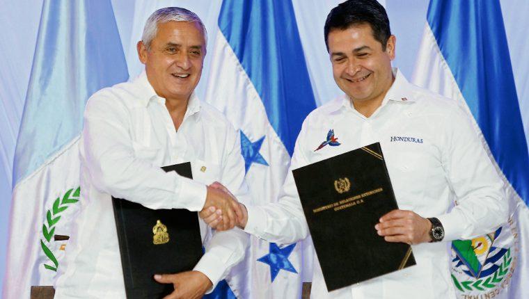 Los presidentes , Otto Pérez Molina y Juan Hernández muestran el documento en donde firmaron el compromiso. (Foto Prensa Libre: Hemeroteca PL).