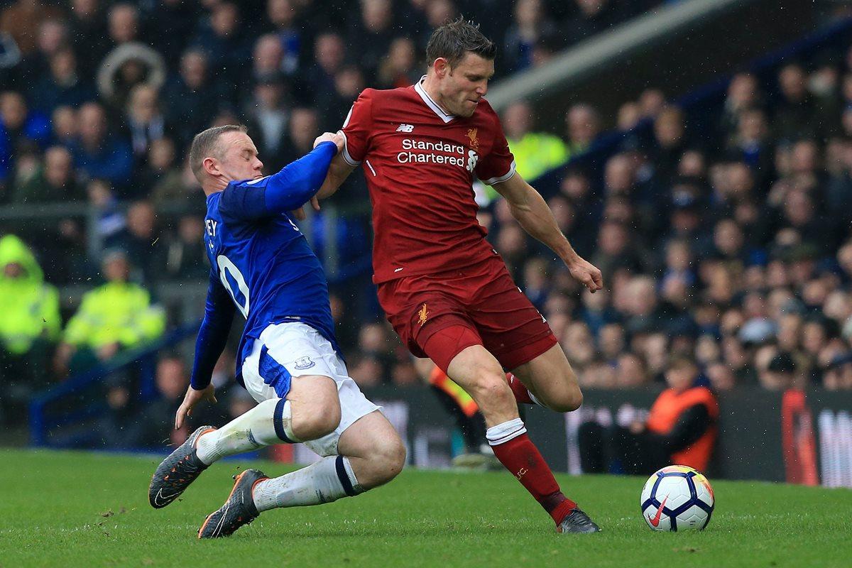 Wayne Rooney trata de detener a James Milner en el duelo entre el Liverpool y el Everton. Foto Prensa Libre: AFP)