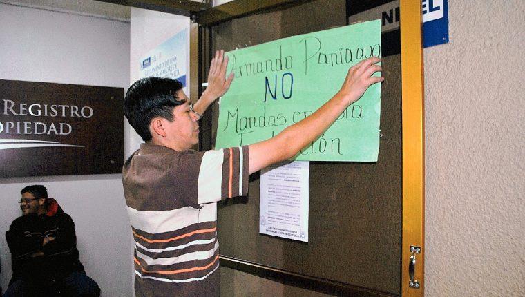 Empleado del Segundo Registro de la Propiedad en Quetzaltenango coloca rótulo en rechazo a la injerencia de Armando Paniagua en esa institución. (Foto Prensa Libre: Alejandra Martínez)
