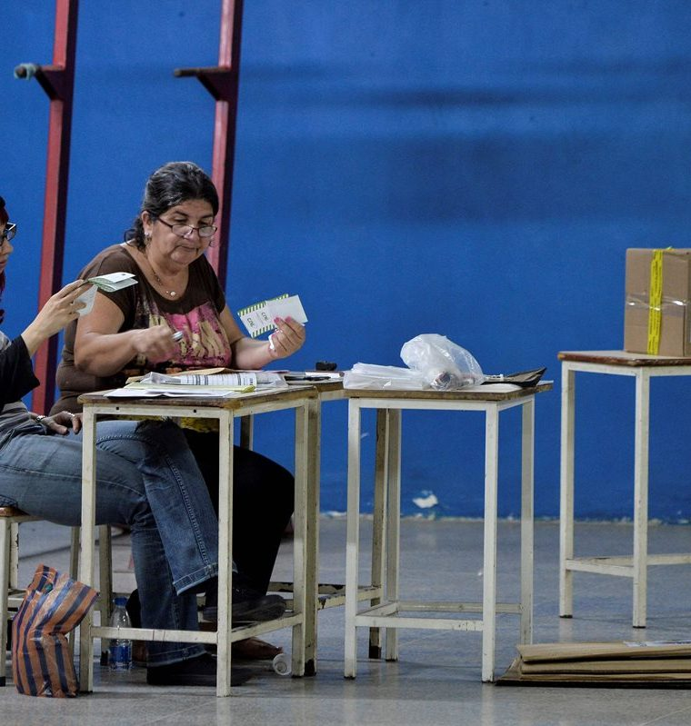Dos mujeres hacen conteo de votos después del cierre de los centros de votación. (Foto Prensa Libre: AFP)