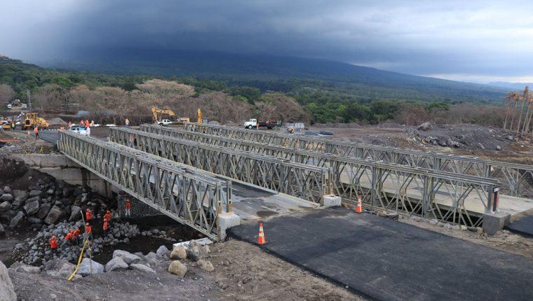 El martes último aún se colocaba una capa de asfalto en el tramo que conecta con el puente Bailey sobre la barranca Las Lajas. (Foto Prensa Libre: Enrique Paredes).