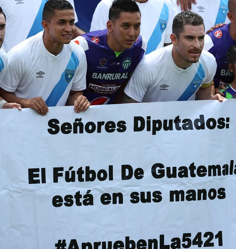 Jugadores cremas muestran una manta con un mensaje dirigido a los diputados del Congreso de la República antes del juego contra Antigua GFC. (Foto de Francisco Sánchez).