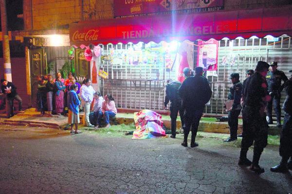 Familiares y  vecinos observan el cuerpo de Elmer Antonio López, de 32 años, quien fue asesinado frente a una tienda en Boca  del Monte. (Foto Prensa Libre: CVB)