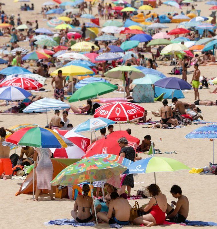 Numerosas personas toman el sol en la playa de Santo Amaro en Oeiras, cerca de Lisboa, Portugal. (Foto Prensa Libre: EFE)