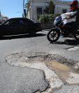 En pleno Centro Histórico, en la 3a. avenida y 13 calle, zona 1, se observan grandes agujeros en el asfalto. En la planificación de la comuna capitalina no se contempla el bacheo en ese sector. (Foto Prensa Libre: Érick Ávila)