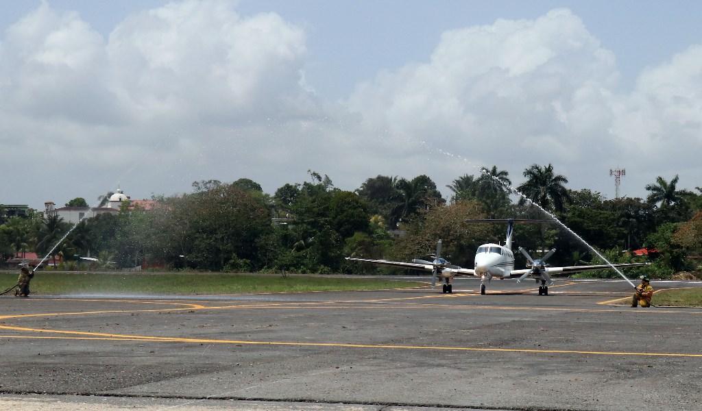 Bomberos Voluntarios lanzan agua al primer vuelo oficial que aterriza en el aeropuerto La Tierra de Dios, de Puerto Barrios, Izabal. (Foto Prensa Libre: Dony Stewart)