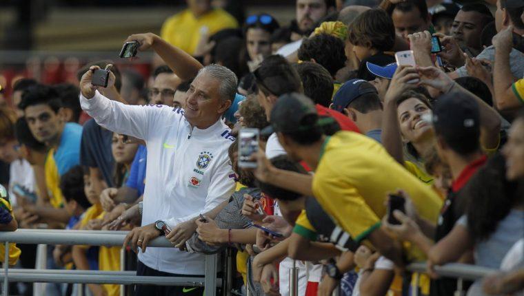 El entrenador de Brasil, Tite se toma una selfie con los aficionados que llegaron al entrenamiento. (Foto Prensa Libre: EFE)