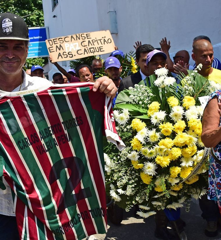 A man shows a shirt of Brazilian team Fluminense with the name of former capitan of Brazil's 1970 World Cup winning team, Carlos Alberto Torres during his burial at Irajá cemetery in Rio de Janeiro, Brazil on October 26, 2016.Carlos Alberto, the revered captain of Brazil's 1970 World Cup-winning side, considered one of the greatest of all time, died on Tuesday aged 72. The right-back starred alongside Pele, Tostao, Jairzinho and Rivelino in the legendary Brazil team that beat Italy 4-1 in the 1970 final. / AFP PHOTO / TASSO MARCELO