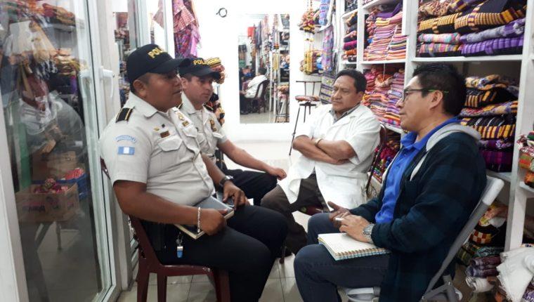 Agentes de la Policía Nacional Civil se reunieron con los comerciantes en un puesto del mercado La Democracia.(Foto Prensa Libre: Fred Rivera)