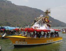 El Niño Dios de Amatitlán es colocado por el párroco en una balsa bellamente decorada, seguida de lanchones que transportan romeristas y músicos durante el cortejo.