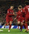 Roberto Firmino (centro), festeja con sus compañeros después de haber marcado un gol para el Liverpool en el juego contra el Arsenal. (Foto Prensa Libre: AFP).