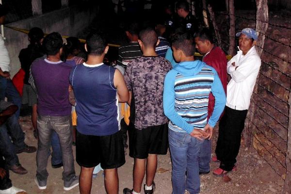 Vecinos observan el lugar donde fue hallado el cuerpo apuñalado de Rigoberto Sánchez Rodríguez, en San Agustín Acasaguastlán, El Progreso. (Foto Prensa Libre: Héctor Contreras)