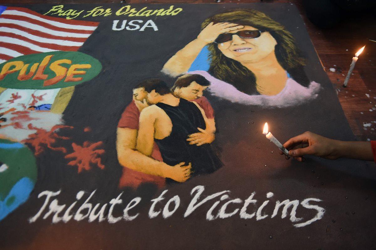 Un lienzo en memoria de las víctimas de la matanza en la discoteca gay de Orlando, EE. UU., es exhibido en la India. (Foto Prensa Libre: AFP).