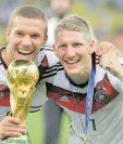Lukas Podolski y Bastian Schweinsteiger junto al trofeo de la Copa del Mundo que ganaron en el Mundial de Brasil 2014. (Foto Prensa Libre: Hemeroteca PL)