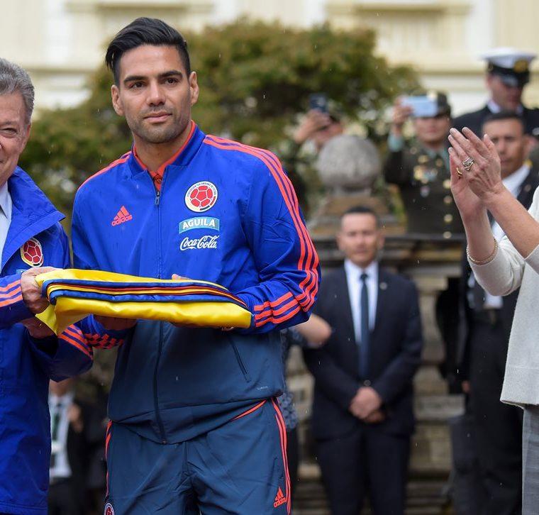 El presidente colombiano Juan Manuel Santos junto a Radamel Falcao durante la ceremonia que le entregó el pabellón a la selección cafetera. (Foto Prensa Libre: AFP)