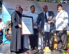 El vicepresidente Juan Alfonso Fuentes Soria entrega el acuerdo de patrimonio a autoridades municipales y religiosas de Esquipulas. (Foto Prensa Libre: Vicepresidencia)