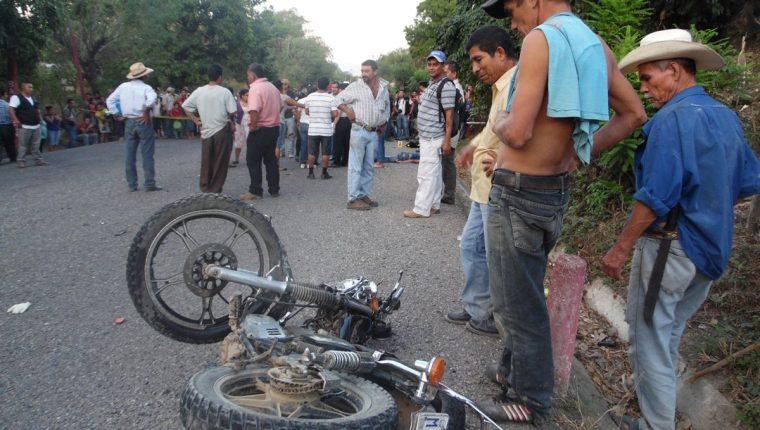 Testigos observan la motocicleta en la que se movilizaban los hermanos Gutiérrez. (Foto Prensa Libre: Víctor Gómez)
