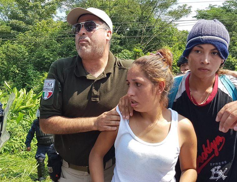 Agentes custodian a una pareja de migrantes hondureños detenidos. (Foto Prensa Libre: Cortesía agencia Xinhua)