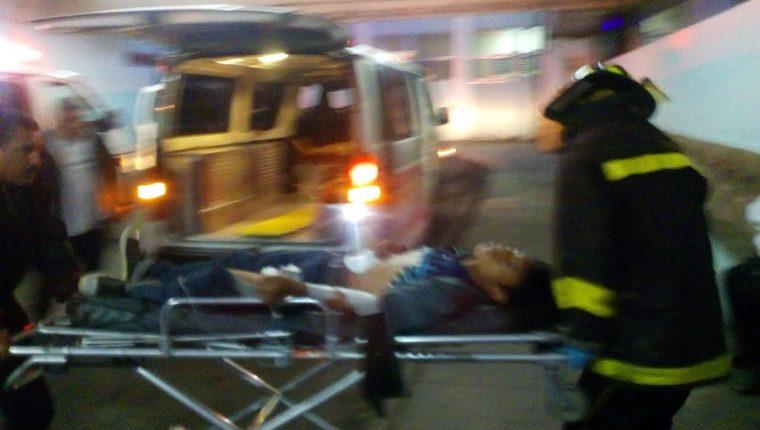 Bomberos ingresan a la emergencia del Hospital General a uno de los trabajadores baleados. (Foto Prensa Libre: Bomberos Voluntarios)