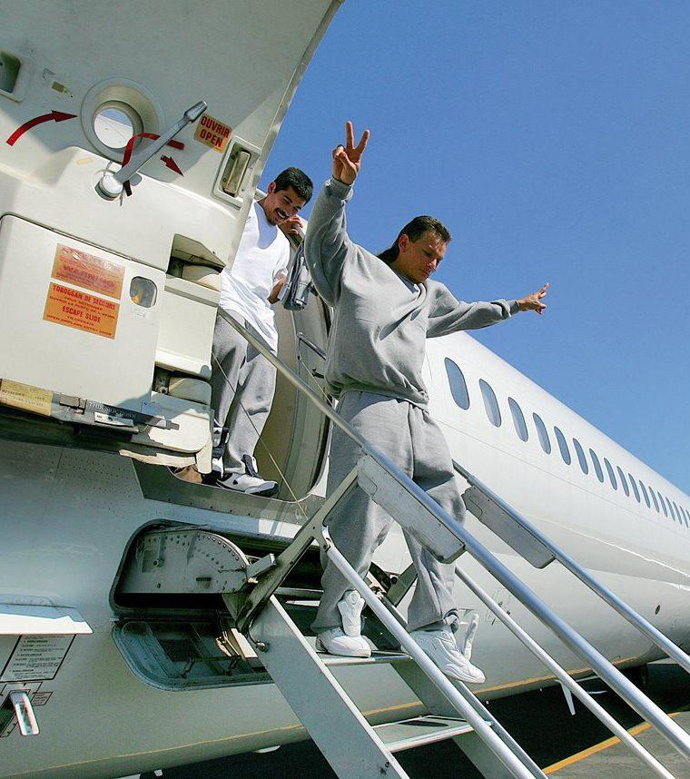 Un deportado da el signo de la paz al llegar a la pista de aterrizaje en el aeropuerto de San Salvador, El Salvador.(Foto HemerotecaPL).