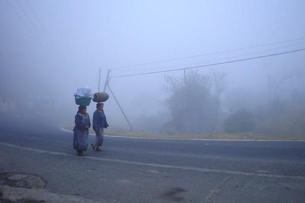 Dos mujeres caminan abrigadas por una calle de  Xelajú, debido a la baja temperatura. (Foto Prensa Libre: ARCHIVO).