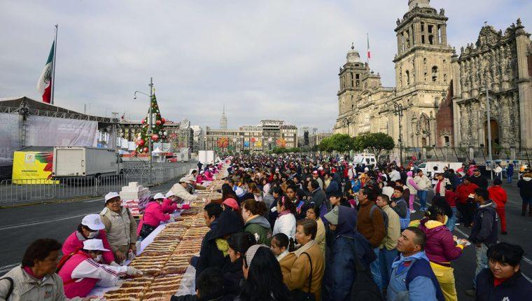 Cientos de personas en el Zócalo de la ciudad de México acuden a adquirir la tradicional Rosca de Reyes. (Foto Prensa Libre: AFP)
