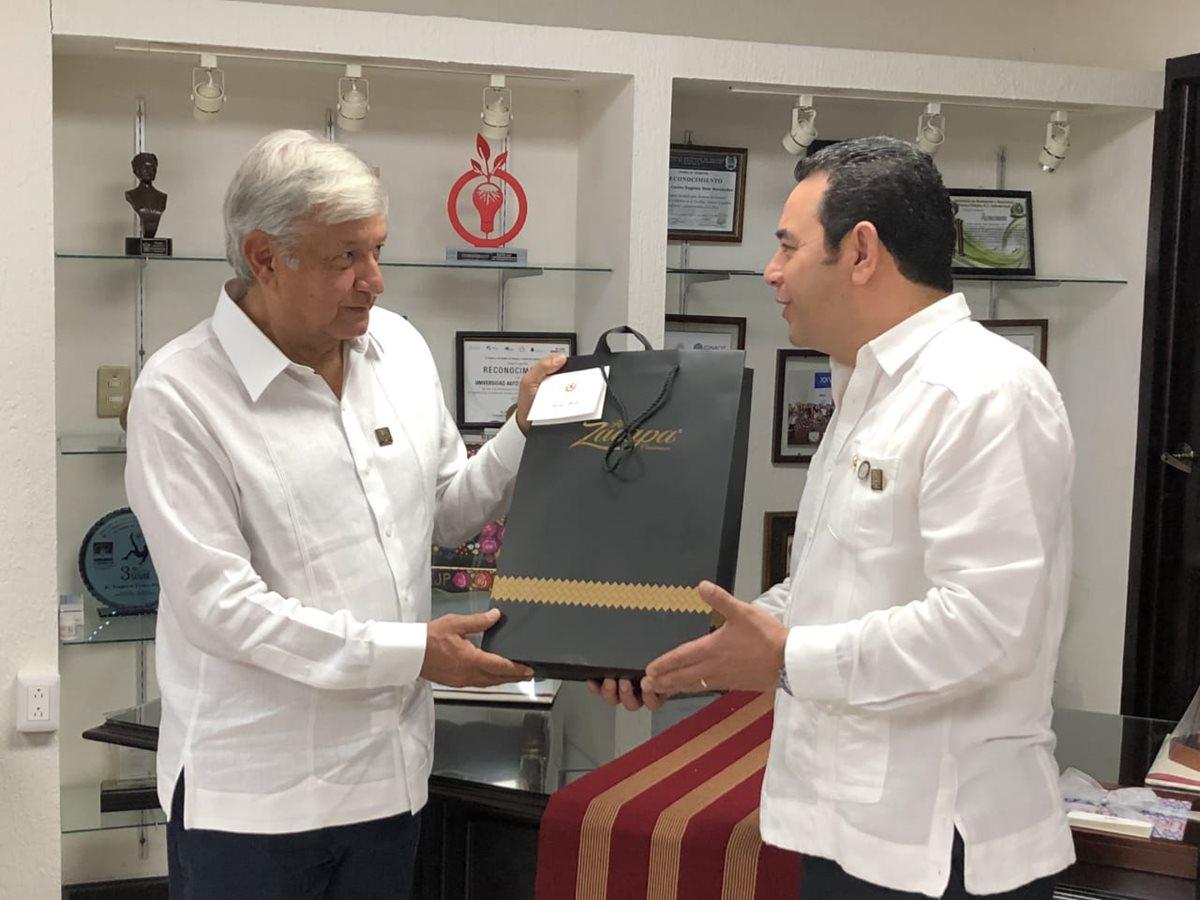 El presidente Jimmy Morales entrega una botella de ron como obsequio al mandatario electo de México, Andrés Manuel López Obrador. (Foto Prensa Libre: SCSP)