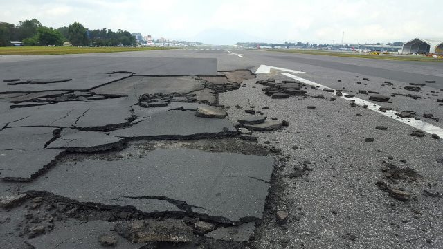 La lluvia y presión de turbinas dañaron la pista inactiva del Aeropuerto Internacional La Aurora. (Foto Prensa Libre: DGAC)