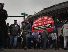 Aficionados de los Cachorros llegan al Wrigley Field pese a la lluvia que afectó en el partido inicial de los campeones. (Foto Prensa Libre: AFP)