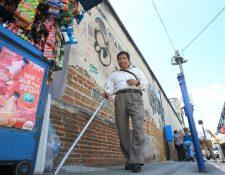 Julián Velásquez, persona no vidente , encuentra obstáculos durante su camina por la 4a. avenida, zona 1. (Foto Prensa Libre: Esbin García)