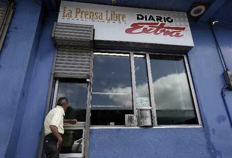 Un hombre espera en una ventanilla del Diario Extra de Costa Rica para ser antendido. (Foto Prensa Libre: EFE).