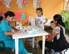 Una madre acude a la jornada médica y lleva a sus hijos a la clínica de pediatría. (Foto Prensa Libre: Rigoberto Escobar)