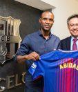 Eric Abidal posa junto al presidente del FC Barcelona Josep Bartomeu. (Foto Prensa Libre: AFP).